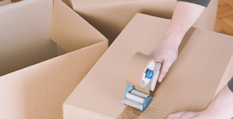 man-sealing-a-shipping-cardboard-box-TL52E9SA